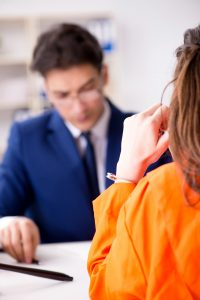 attorney reading a paper in front of a inmate