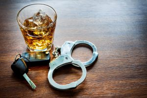 glass of alcohol next to handcuffs and keys
