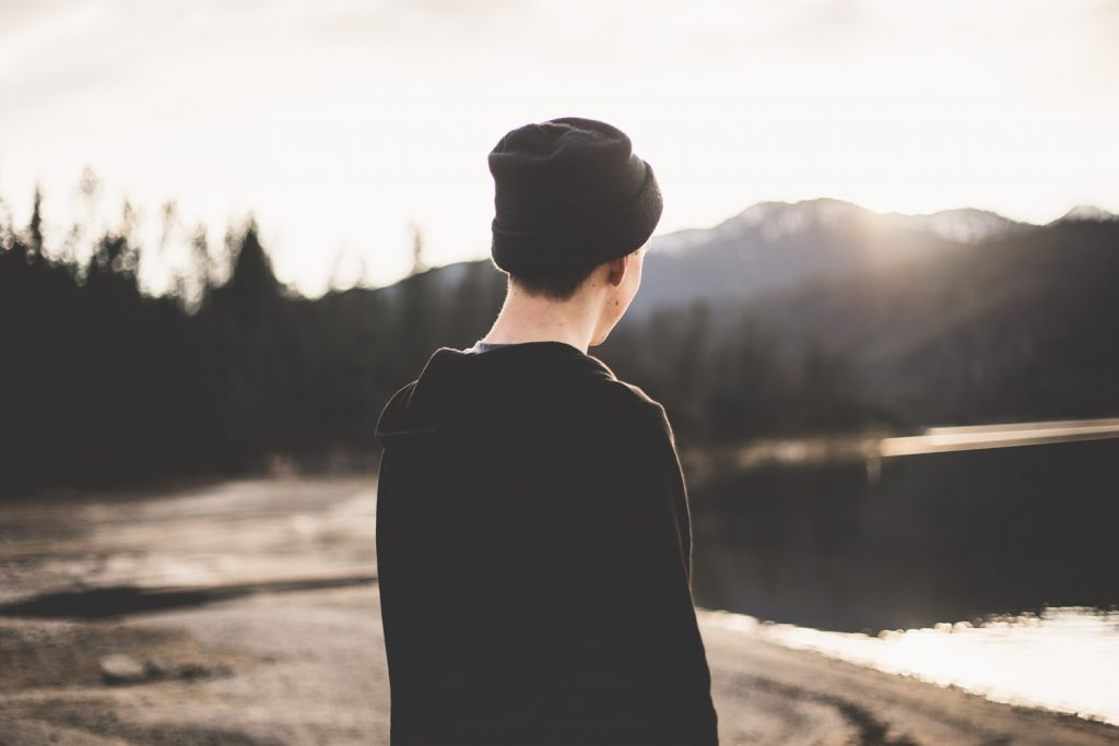 Man with beanie staring at mountains