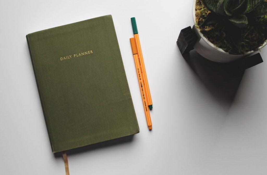 dark green planner next to two pencils